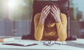 Frustrated woman seated at her office desk with her head in her hands.